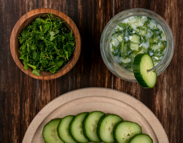 Top view of chopped greens with okroshka and cucumbers on a stand on a wooden surface