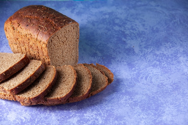 Top view of chopped in half black bread slices on the right side on light ice blue pattern background with free space