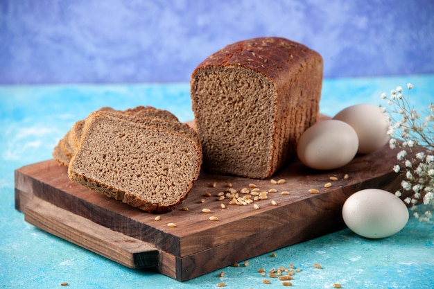 Top view of chopped in half black bread slices on wooden boards flower eggs on light ice blue background