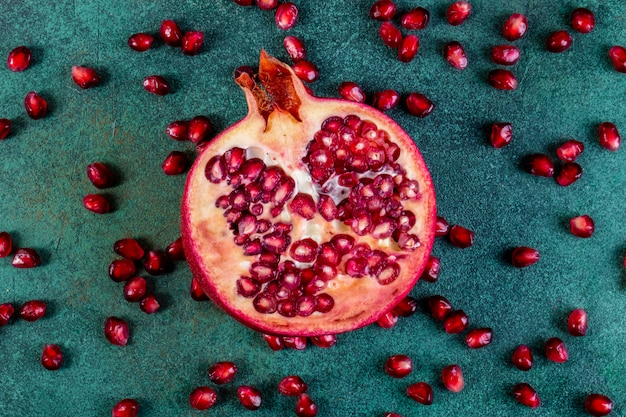 Top view chopped half pomegranate with peeled on a green table