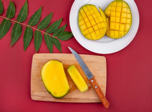 Vista dall'alto di mango tritato con coltello sul bordo di cucina in legno con mango a fette in un piatto bianco con foglia sul rosso