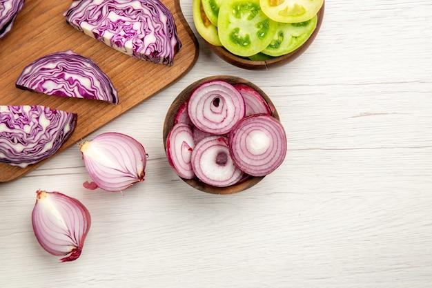 상위 뷰 나무 보드에 붉은 양배추를 잘게 잘린 녹색 토마토는 흰색 테이블 여유 공간에 그릇에 양파를 잘라