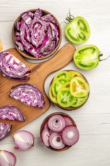 상위 뷰 나무 보드에 붉은 양배추를 잘게 잘라 양파는 흰색 테이블에 그릇에 그린 토마토를 잘라