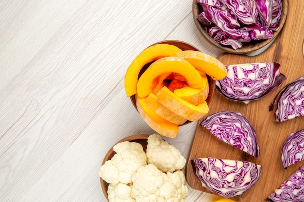 Top view chopped red cabbage on wood board cauliflower cut pumpkin in bowls on white table free space