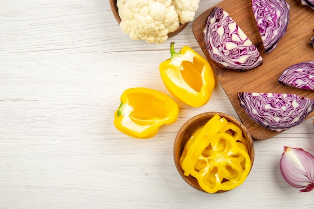 Top view chopped red cabbage on wood board cut onion cut yellow bell peppers cauliflower in bowls on white table free space