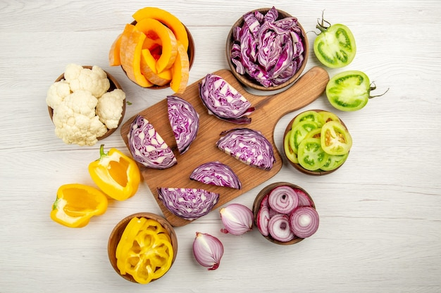 Top view chopped red cabbage on wood board cut pupmkin cut green tomatoes cut yellow bell peppers in bowls on white surface