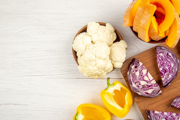 Top view chopped red cabbage on wood board cut yellow bell peppers cauliflower cut pumpkin in bowls on white table free place