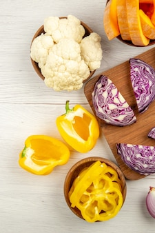 Top view chopped red cabbage on wood board cut yellow bell peppers cut pumpkin in bowl on white table