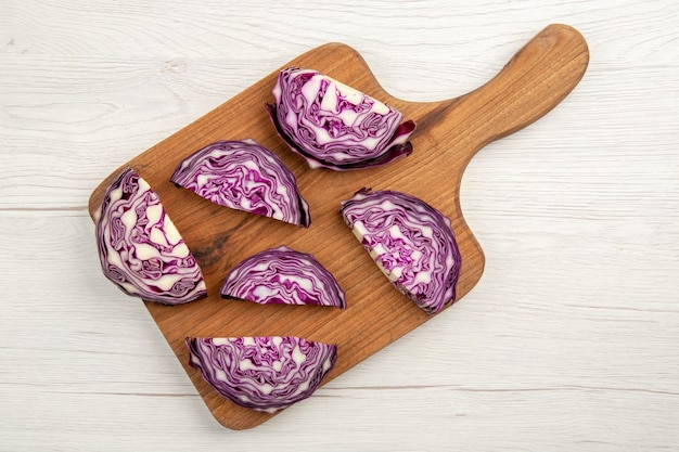 Top view chopped red cabbages on cutting board on white surface