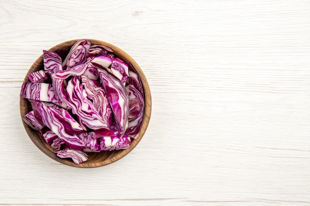 Top view chopped red cabbages in wooden bowl on white surface with free space