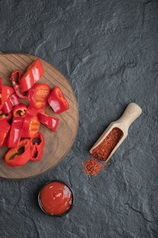Top view of chopped red pepper with peppercorn and ketchup.