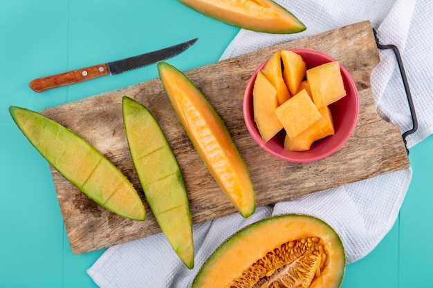Top view of chopped slices of cantaloupe melon on wooden kitchen board with knife on blue