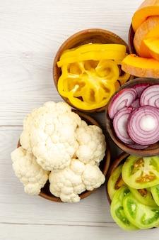 上面図みじん切り野菜カットカボチャカット黄色ピーマンカットタマネギカットグリーントマトカリフラワーボウルに白いテーブル
