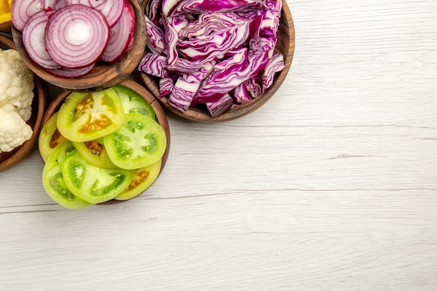 Top view chopped vegetables cut red cabbage cut onion cut green tomatoes cauliflower in bowls on white table free space