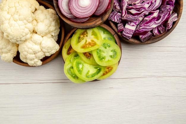Vista dall'alto le verdure tritate tagliate il cavolo rosso tagliato la cipolla tagliata i pomodori verdi il cavolfiore in ciotole sul tavolo bianco spazio libero