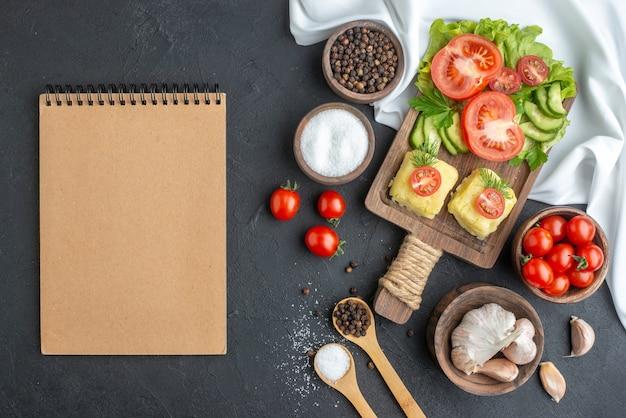 Vista dall'alto di verdure fresche tritate e intere sul tagliere in ciotole e spezie notebook su asciugamano bianco su superficie nera