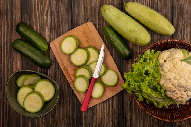 Top view of chopped zucchinis on a bowl with chopped zucchinis on a wooden kitchen board with knife with cauliflower and lettuce on a bucket with cucumber and zucchinis isolated on a wooden wall