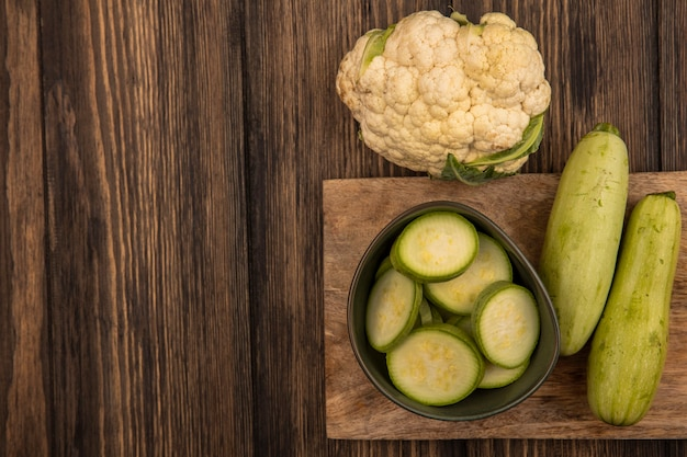 Top view of chopped zucchinis on a bowl on a wooden kitchen board with lettuce zucchinis and cauliflower isolated on a wooden wall with copy space