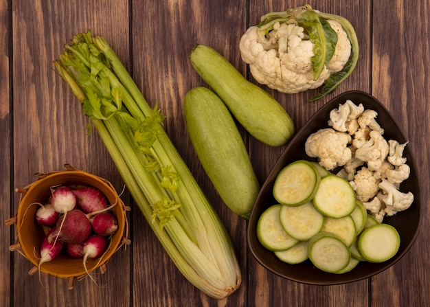 Top view of chopped zucchinis and cauliflower buds on a bowl with radishes on a bucket with whole zucchinis celery and cauliflower isolated on a wooden surface