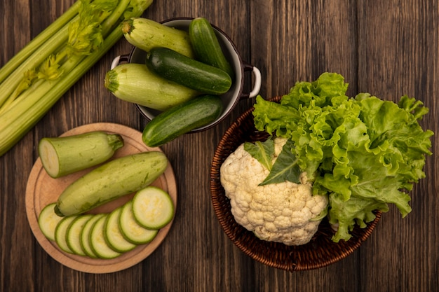 Top view of chopped zucchinis on a wooden kitchen board with cucumbers on a bowl with cauliflower and lettuce on a bucket with celery isolated on a wooden background
