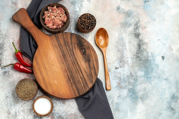 Top view chopping board black tablecloth bowls with meat different spices wooden spoon on nude surface copy space