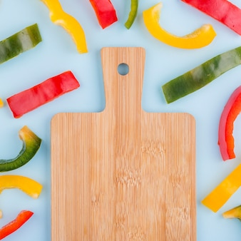Top view chopping board surrounded by bell peppers