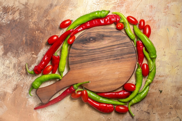 Top view a chopping board surrounded by peppers and cherry tomatoes on amber background