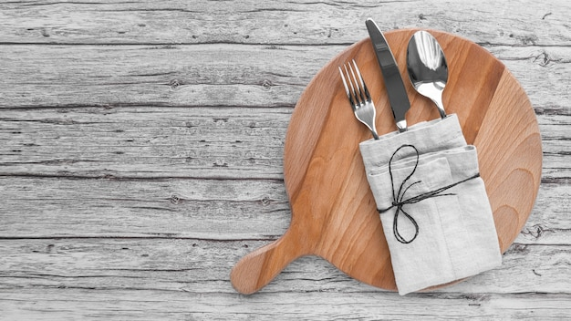 Top view of chopping board with cutlery wrapped in cloth