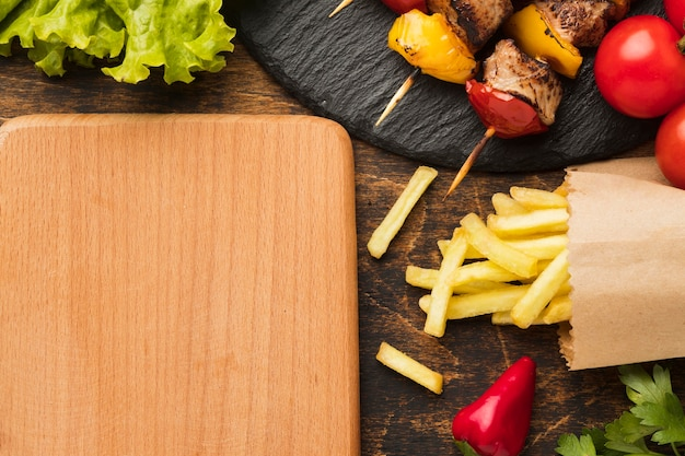 Top view of chopping board with delicious kebab and french fries