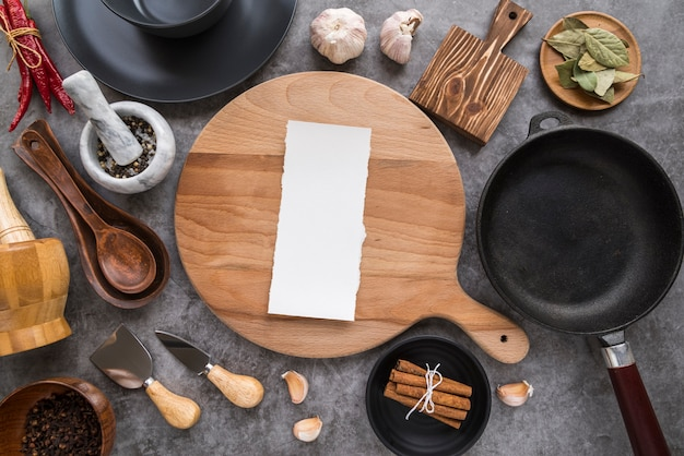 Top view of chopping board with paper menu and pan