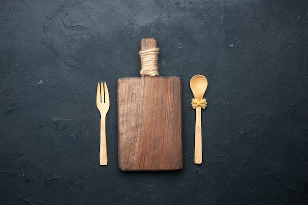 Top view chopping board wooden spoon and fork on dark surface copy space