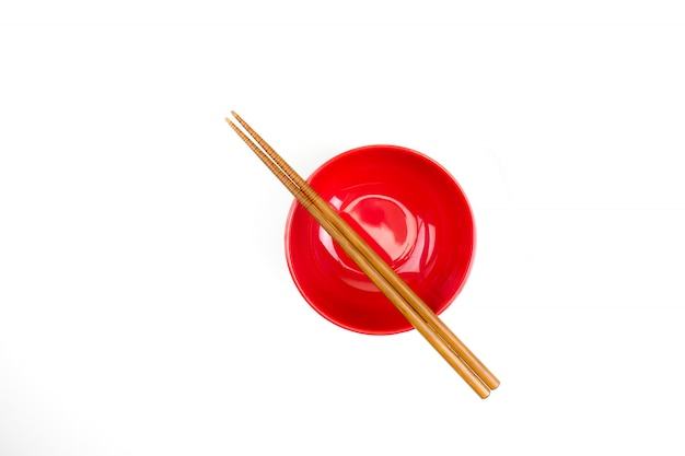Top view of chopsticks placed on a red bowl.