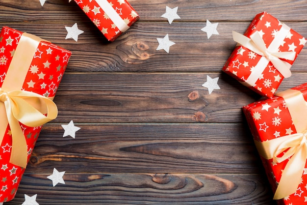 Top view of christmas background made of gift boxes and stars on wooden background. new year holiday concept with copy space