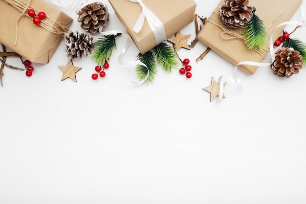 Vista dall'alto della composizione in natale con confezione regalo, nastro, rami di abete, coni, anice sul tavolo bianco