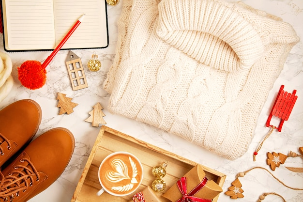 Top view over christmas composition with warm sweater, gifts, xmas lights and coffee