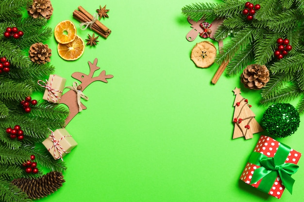 Top view of christmas decations on green background. new year holiday concept with copy space