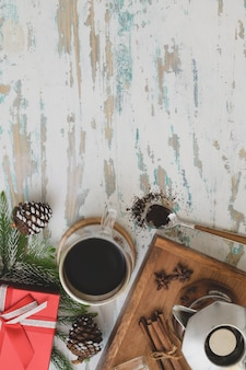 Top view of christmas decorated workplace coffee cup and present on vintage wooden desk