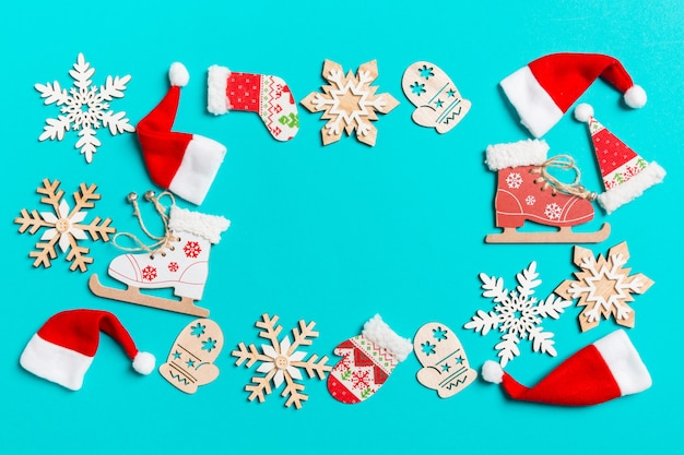 Top view of christmas decorations and santa hats on blue background. happy holiday concept with copy space