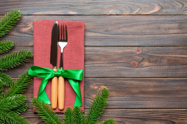 Top view of christmas decorations on wooden background. fork and knife on napkin tied up with ribbon and empty space . new year pattern