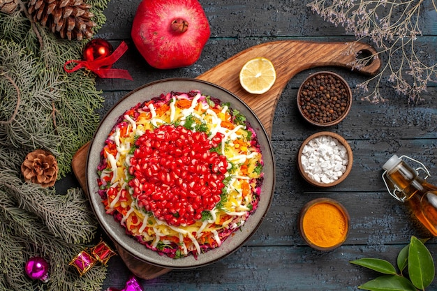 Top view christmas dish christmas dish on the board next to the pomegranate colorful spices oil and branches with cones christmas tree toys