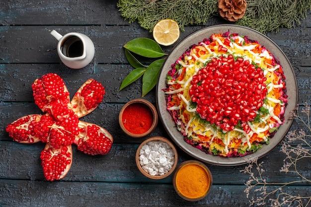 上面図クリスマス料理スパイスのクリスマス料理ボウルレモンスプルースの枝とコーンオイルの丸薬ザクロの横