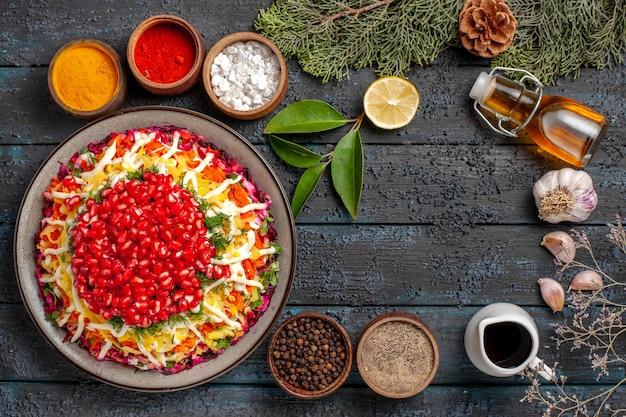 Vista dall'alto piatto di natale con bottiglia di melograno di olio aglio accanto alle ciotole di diverse spezie rami di abete rosso con coni sul tavolo