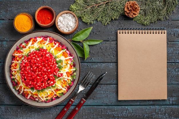 さまざまなスパイスのクリーム色のノートブックボウルの横にザクロのニンジンポテトがテーブルにコーンが付いているトウヒの枝が付いている上面図のクリスマス料理