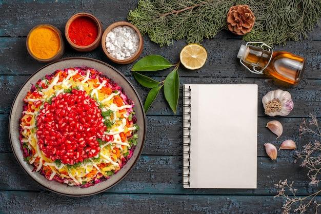 テーブルの上にコーンが付いているスパイスの枝の白いノートブックボウルの横にザクロの油のボトルの種子が付いている上面図のクリスマス料理