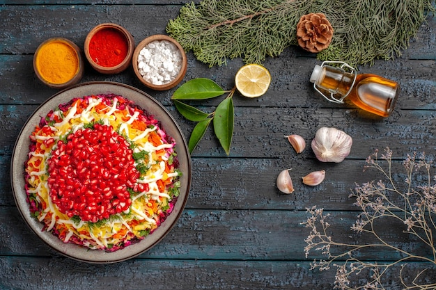 Top view christmas dish dish with seeds of pomegranate bottle of oil bowls of spices lemon garlic spruce branches with cones on the table