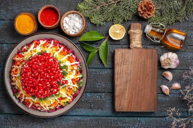 Top view christmas dish dish with seeds of pomegranate bottle of oil next to the cutting board bowls of spices lemon garlic spruce branches with cones on the table