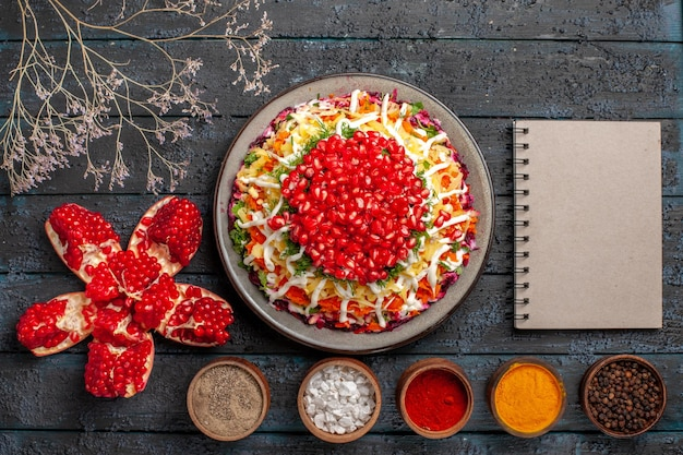 Vista dall'alto ciotole di cibo natalizio di spezie colorate melograno sbucciato accanto al quaderno grigio piatto di natale con patate carote barbabietole melograno e maionese e rami di albero