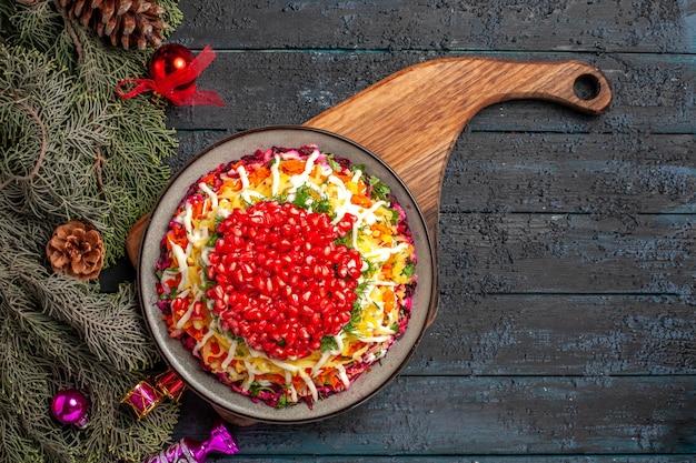 Vista dall'alto cibo natalizio piatto natalizio con melograno sul tagliere e rami di abete rosso con giocattoli per l'albero di natale