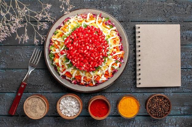 Vista dall'alto cibo natalizio cinque ciotole di spezie accanto alla forchetta del taccuino bianco piatto natalizio con melograno e rami di albero