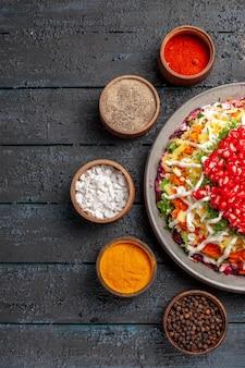 Vista dall'alto piatto di cibo natalizio di appetitoso piatto natalizio con semi di melograno accanto ai rami degli alberi e cinque ciotole di spezie colorate sul tavolo
